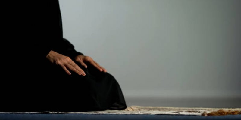 Young female in hijab praying on mat, asking god forgiveness, religious ritual
